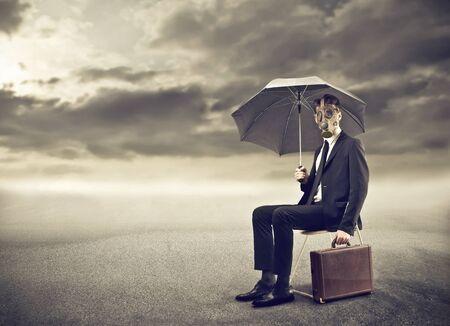 lonliness: businessman wearing a gas mask under an umbrella Stock Photo
