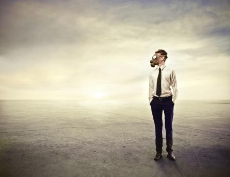 lonliness: businessman wearing a gas mask Stock Photo