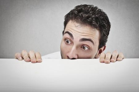man behind: man hiding behind a table