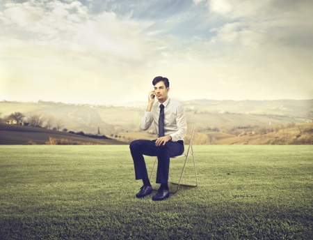 quietness: businessman phoning in the countryside