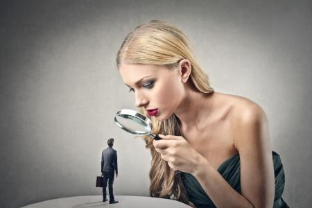 loupe: femme regarde un homme d'affaires � travers une loupe Banque d'images
