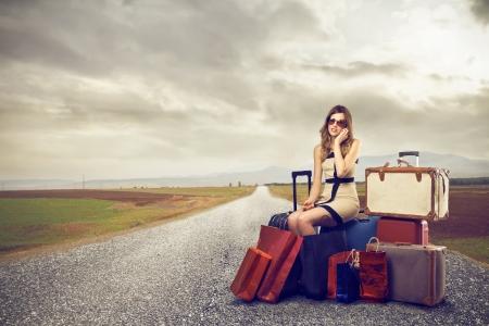 通りの真中でスーツケースの多くとファッション女性 写真素材