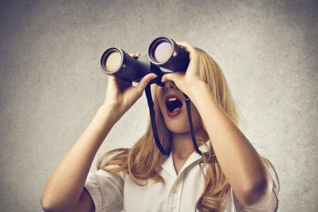놀라게 여자는 쌍안경으로 뭔가 찾고