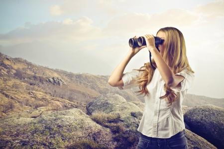 descubrir: Mujer que mira algo con binoculares