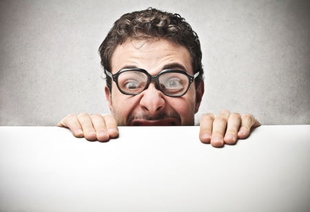 fear face: scared man hiding behind a table