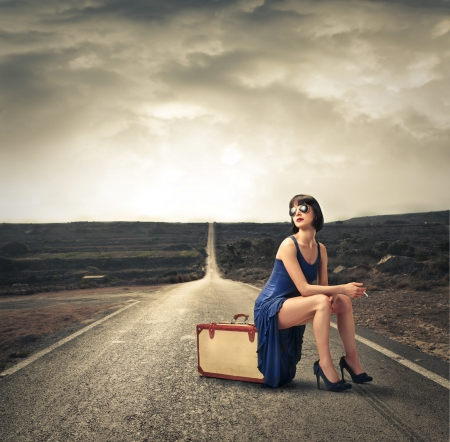 Fashion woman sitting on her luggage photo