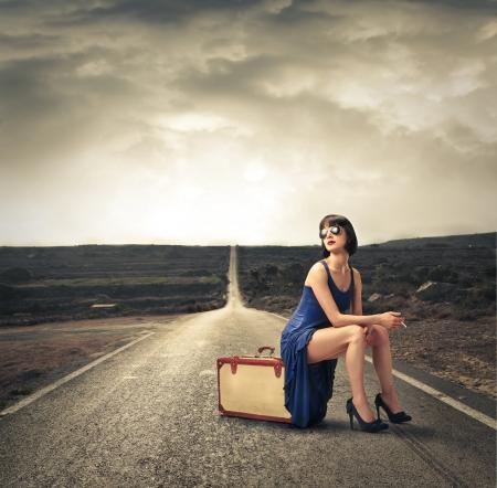 mujer sentada: Forme a la mujer que se sienta en su equipaje Foto de archivo