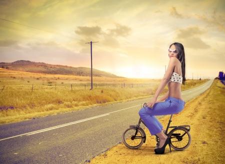 beautiful fashion woman riding a bike photo