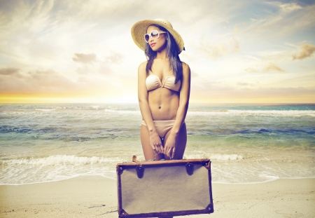beautiful woman in bikini holding a suitcase photo