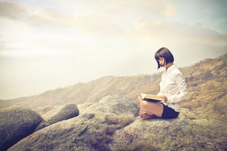 donna lettura su una roccia Archivio Fotografico