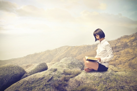 calm woman: woman reading on a rock