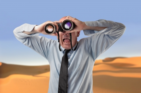 stupor: scared businessman using a binoculars Stock Photo