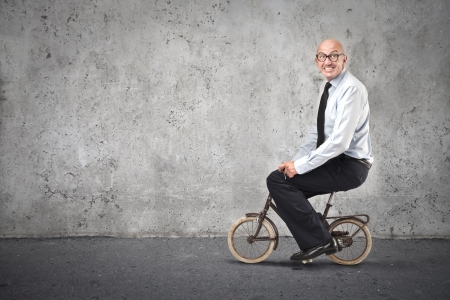 optimism: businessman riding a small bike Stock Photo