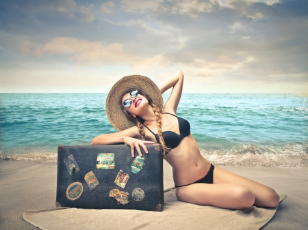 woman sunbathing hold to her suitcase photo