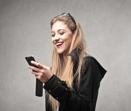 young woman smiling checking her phone Stock Photo - 21803075
