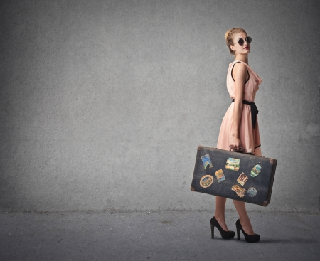 fashion woman with her suitcase ready to leave photo