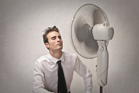 businessman feeling hot in front of a fan