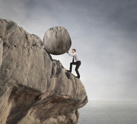 risky situation: businessman trying to holding a huge rock