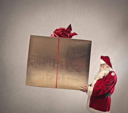 christmas costume: Father Christmas holding a huge present Stock Photo