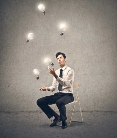 expertise concept: businessman playing with some light bulbs