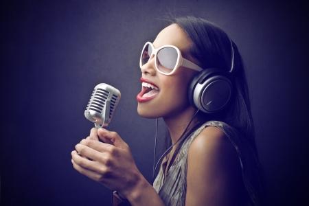 schöne junge Frau singt Standard-Bild