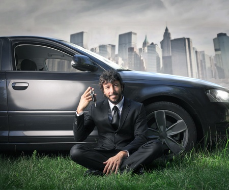businessman sitting on the grass holding his car s key photo