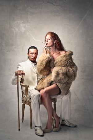 金持ち: 金持ちが彼の膝の上に座っている女性と椅子に座って