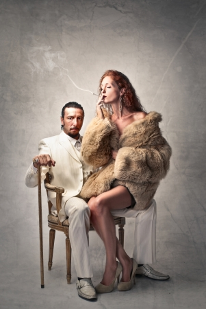 rich man sitting on a chair with a woman sitting on his lap
