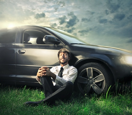 car wheels: businessman relaxing sitting on the grass with his car Stock Photo