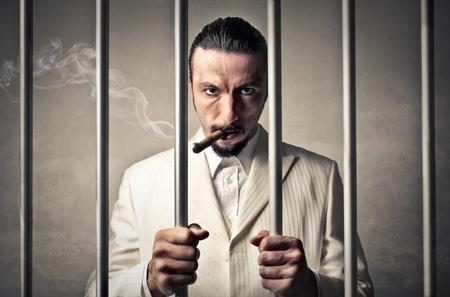 imprisonment: rich boss man into jail  Stock Photo