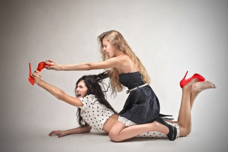 women fighting for a pair of red shoes Stock Photo