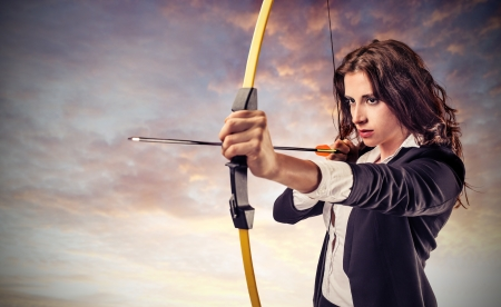 business woman aiming with bow and arrow photo