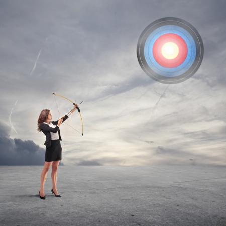 concept: zakelijke vrouw gericht met behulp van pijl en boog