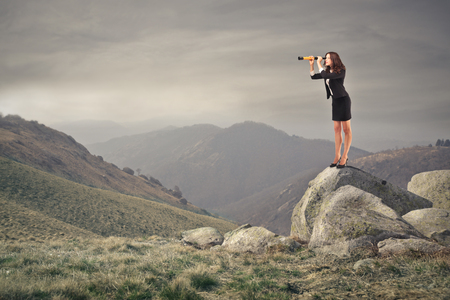 business woman looking through a binoculars on the top of a rock