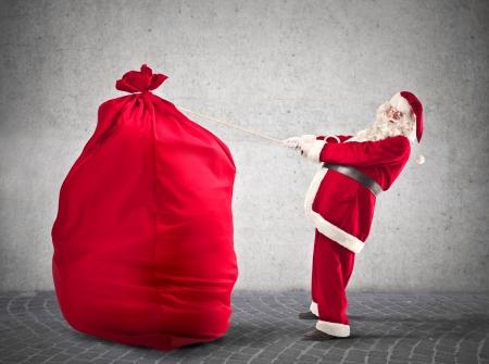 big: Santa Klaus trying to carrying a huge bag  Stock Photo