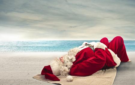 chapeaux: Santa Klaus d�tente sur la plage Banque d'images