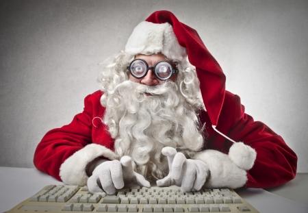 Nerd Santa Klaus using a computer