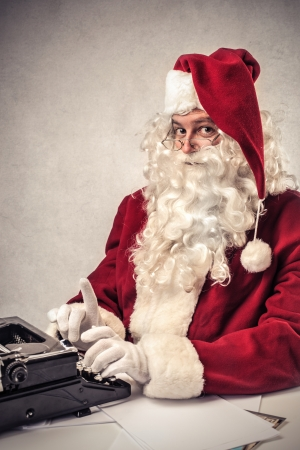 Santa Klaus typing on a typewriter  Stock Photo