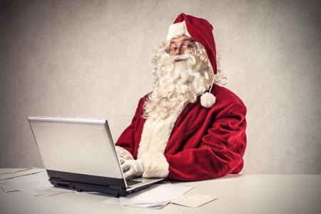 Kerstman Klaus met behulp van een laptop