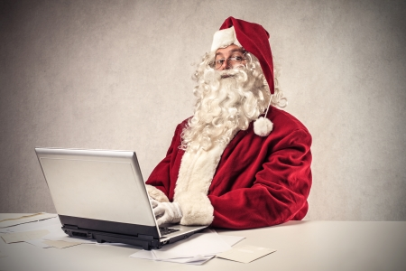 christmas costume: Santa Klaus using a laptop