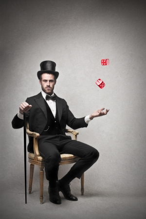lucky man: rich man sitting on a chair throwing the dice Stock Photo