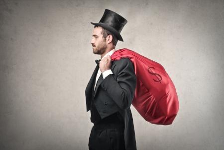 rich man: hombre rico con una bolsa de color rojo lleno de dinero