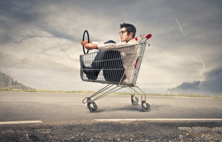 shopping man: businessman into a cart pretending to drive a car Stock Photo