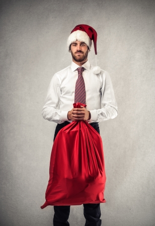 handsome businessman with a Christmas  hat and a red bag Stock Photo - 22756638