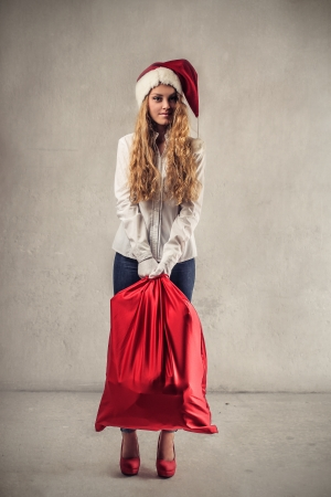 young woman with a Christmas  hat and a red bag Stock Photo - 22756640