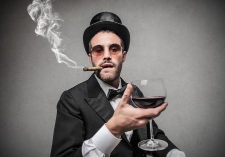 cilindro: hombre rico con un vaso de vino y fumar un cigarro Foto de archivo