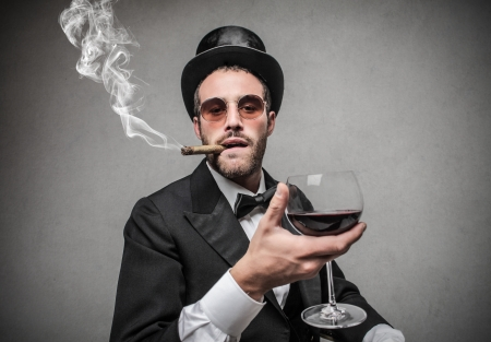 rich man holding a glass of wine and smoking a cigar photo