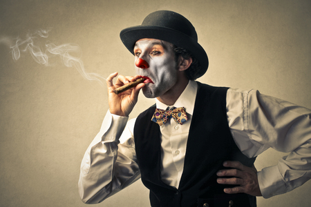 clowngesicht: Clown raucht eine Zigarre