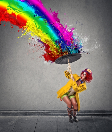 ironic: clown protecting herself from a paint-rainbow Stock Photo