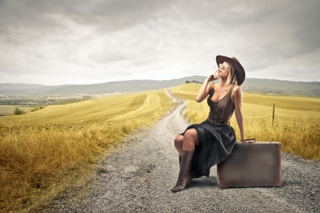 woman waiting sitting on her suitcase smoking photo